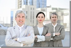 Portrait of three business people outside.
